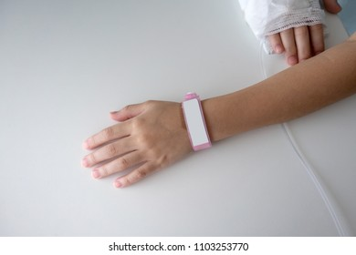 Kid hand wearing the pink plastic name tag isolated on white background