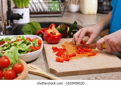 Kid hands chopping red bellpepper for a delicious vegetable salad - closeup on cutting board in the kitchen, shallow depth