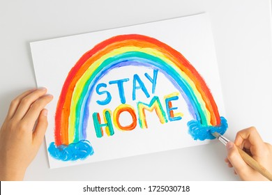 Kid hands painting during quarantine at home. Rainbow with words Stay at home. Social media campaign for coronavirus prevention