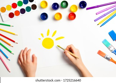 Kid hands painting yellow sun. Top view to white table with art supplies
