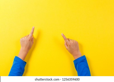 Kid hands pointing to something on yellow background