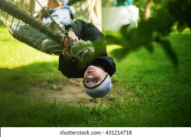 kid hanging hammock upside down backyard background selective focus