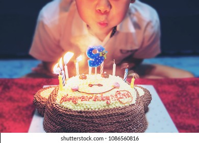 Kid is happily blowing candles on his birthday cake - happy joyful birthday party celebration concept