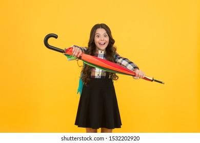 Kid happy schoolgirl with umbrella. Fall weather forecast. Feeling carefree. Rainy september. Adorable small schoolgirl with backpack. Schoolgirl daily life. Girl with umbrella. Happy childhood.