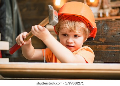 Kid in hard hat holding wooden plank and hammer. Child engineer with carpenter work hammer on wood