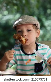 Kid has chicken in the outdoor cafe