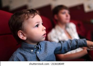 The kid has popcorn in the cinema