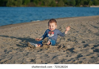 The kid to have fun on the bank of the lake. The little boy sits on sand