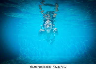 Kid having fun in swimming pool. Underwater portrait of child. Summer vacation