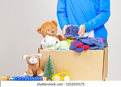 Kid hold Christmas donation box with toys, books, clothing for charity