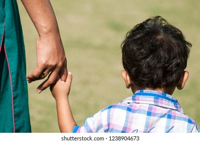 A kid is hold the finger of his mother