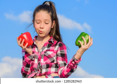 Kid hold ripe pepper harvest. Fall harvest homegrown vegetables. Vegetarian concept. Which pepper would you pick. Kid girl hold red and green peppers sky background. Child presenting kinds of pepper.