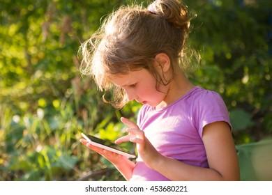 kid hold tablet, phone for playing and education. Little girl using a tablet outdoors.