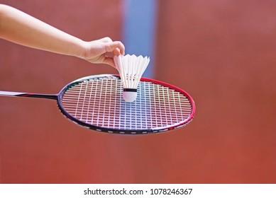kid holding badminton racket and shuttlecock in badminton court.