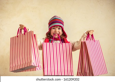 Kid holding Christmas shopping bags in hands