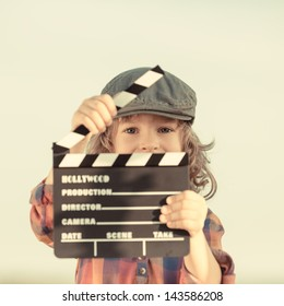 Kid holding clapper board in hands. Cinema concept. Retro style