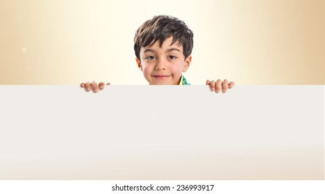 Kid holding empty placard over ocher background