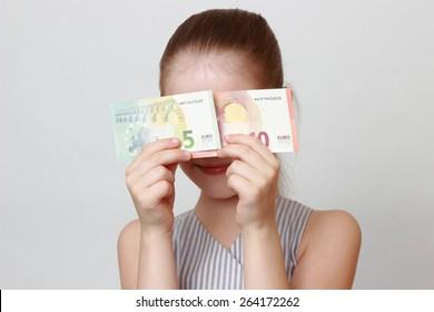 Kid holding euro cash banknotes