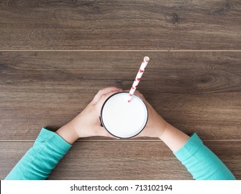 Kid holding glass of milk on dark rustic background