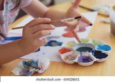 Kid holding paint brush, preschool child painting