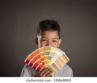 kid holding a pantone palette on a gray background
