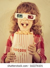 Kid holding popcorn in hands. Cinema concept. Retro style
