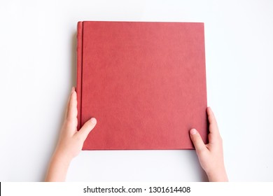 Kid holding red leather covered photobook or album. Photobook lie on white background. Top view.