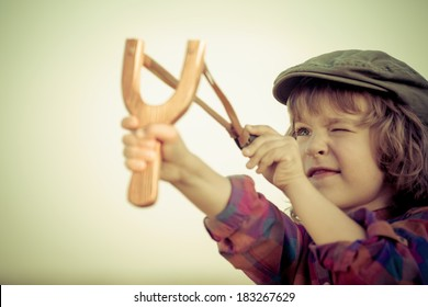 Kid holding slingshot in hands against summer sky background. Retro style