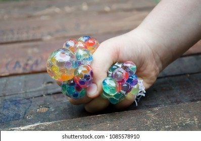 kid holding stress relief grape balls, squeezing balls, mesh squishy balls hand wrist toy, isolated on wooden background