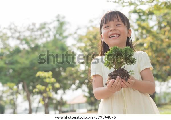 Kind, das eine junge Pflanze in Händen hält auf grünem Hintergrund. Ökokonzept