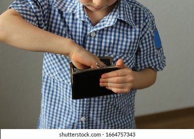 kid holds a wallet and takes out with his hand, the concept of pocket money, theft, shopping - Shutterstock ID 1664757343