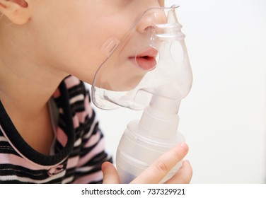 Kid with inhaler isolated on white background. Child holds inhaler mask close-up. Concept of treatment of children's respiratory diseases