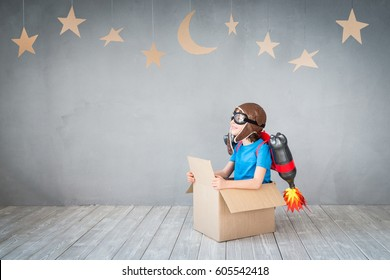 Kid with jet pack looking at cardboard stars. Child playing at home. Success, imagination and innovation technology concept