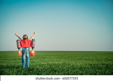 Kid with jet pack outdoor. Child playing in green spring field. Success, imagination and innovation technology concept. Summer travel and adventure