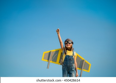 Kid with jet pack pretend to be superhero. Child playing in summer. Kid having fun outdoors. Child pilot against summer sky background. Success, leader and winner concept. Imagination, freedom concept
