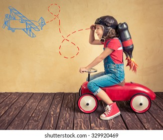 Kid with jetpack driving retro toy car. Child playing at home. Success, leader and winner concept