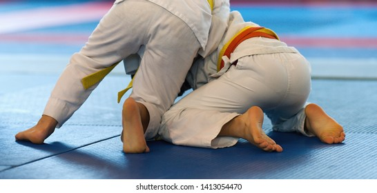 Kid judo, childrens martial art in hall competition at judo school, two little wrestling boys in the fight, effort and attainment