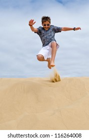 Kid jumping in the sand