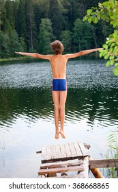 Kid jumps off a wooden dock into the water in a summer forest
