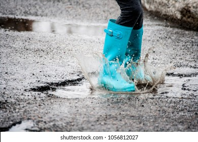 kid jumps in puddle of water