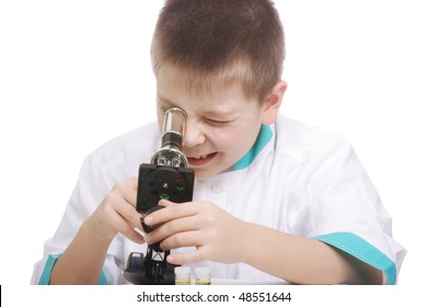 Kid in lab smock looking into microscope against white background