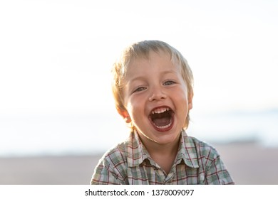 Kid laughing with mouth wide open, enjoying himself.