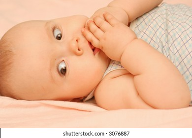 The kid laying on a bed holds hands in a mouth