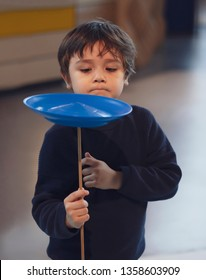 Kid learning how to play spinning plate, Preschool boy balancing bolw on wooden pole, Children learn and play, Indoors or Outdoors activities for kids and family