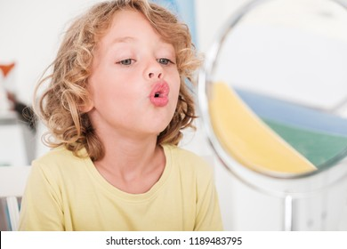 Kid learning to speak in front of a mirror during correct pronunciation classes