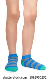 Kid legs in striped socks isolated on white background.