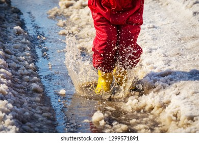 Kid legs in yellow rainboots jumping in the ice puddle with melting snow at sunny spring day, outdoors
