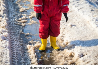 Kid legs in yellow rainboots standing in the ice puddle with melting snow at sunny spring day, outdoors