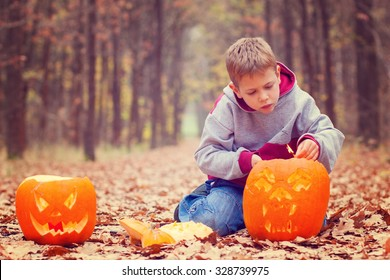 Kid lighting the jack-o- lantern in autumnal forest