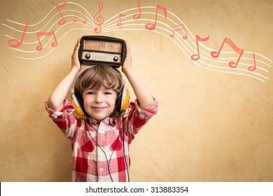 Kid listen music at home. Hipster child with retro vintage radio